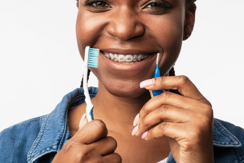 Black Girl With Braces Holding Toothbrushes Posing On White Background