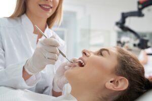 Dentist treating woman's teeth in dentistry