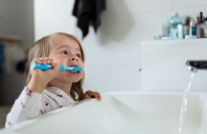 Baby girl in bright bathroom brushing her teeth above the sink