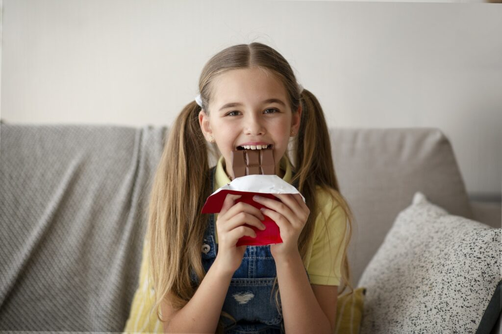 Lady eating chocolate sitting on a couch at home