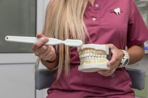 The dentist holds a model of the human jaw in his hands and teaches the patient to properly brush