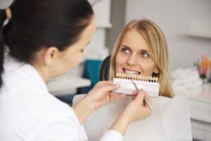 Dentist choosing color teeth from palette