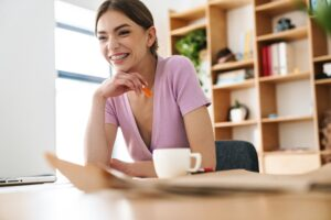 Photo of young joyful woman laughing while working with laptop