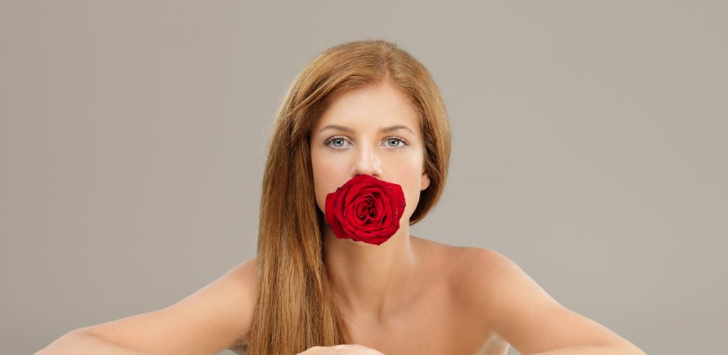 beautiful woman holding red rose in mouth